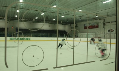Katelyn Landry and Casey Pickett (no. 9 and 11, Team White), shoot on Lauren Slebodnick (no. 30, Team Black) during NWHL Boston Pride free agency training camp at Ristuccia Arena
