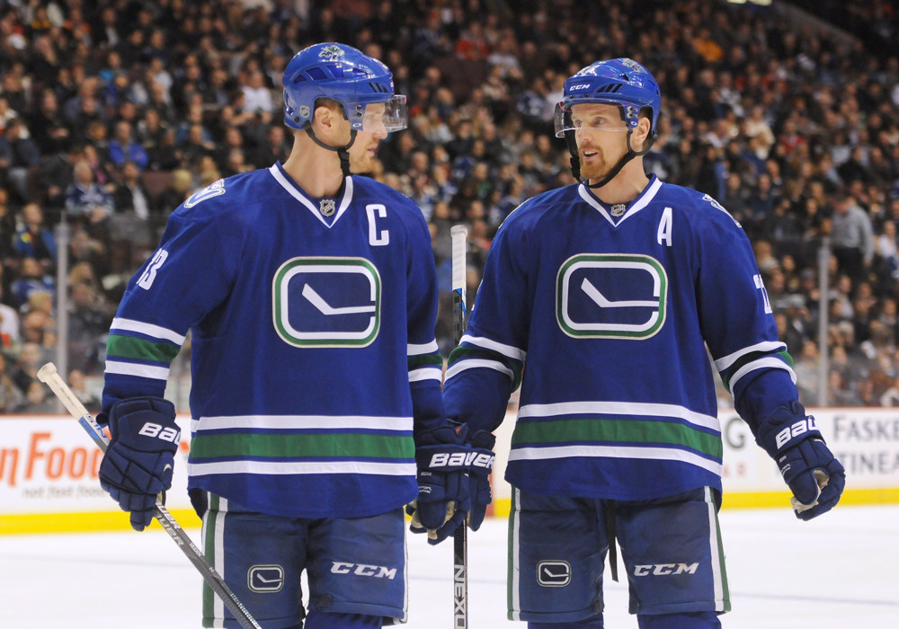 November 21, 2015: Vancouver Canucks Center Henrik Sedin (33) [1917] and Vancouver Canucks Left Wing Daniel Sedin (22) [1911] talk during a break in action against the Chicago Blackhawks on Saturday night in Vancouver, British Columbia.