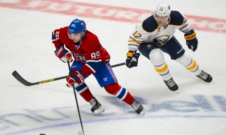 15 September 2013: Kevin Porter #12 of the Buffalo Sabres tries to take the puck from Martin Reway #89 of the Montreal Canadiens during the NHL preseason game at the Bell Centre in Montreal Quebec, Canada